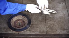 Mechanic man hands compare old worn brake disk with new object. stock footage