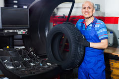 Mechanic man having car wheel on equilibrium control machinery. Mature diligent glad mechanic man having car wheel on equilibrium control machinery in car Royalty Free Stock Photography