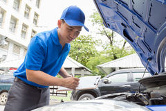 Mechanic man holding clipboard and check the car Stock Photography