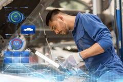 Mechanic man with lamp repairing car at workshop Royalty Free Stock Images