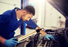 Mechanic man with lamp repairing car at workshop. Car service, repair, maintenance and people concept - auto mechanic man with lamp working at workshop royalty free stock images