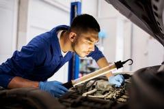 Mechanic man with lamp repairing car at workshop. Car service, repair, maintenance and people concept - auto mechanic man with lamp working at workshop Royalty Free Stock Photos