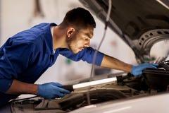 Mechanic man with lamp repairing car at workshop Royalty Free Stock Photos