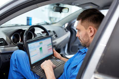 Mechanic man with laptop making car diagnostic royalty free stock photography