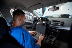 Mechanic man with laptop making car diagnostic Royalty Free Stock Image