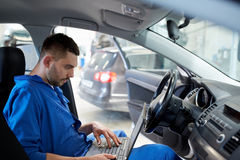 Mechanic man with laptop making car diagnostic Royalty Free Stock Images
