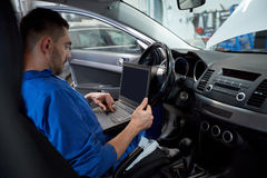 Mechanic man with laptop making car diagnostic Stock Images