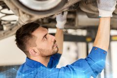 Mechanic man or smith repairing car at workshop. Car service, repair, maintenance and people concept - auto mechanic man or smith working at workshop Stock Photography