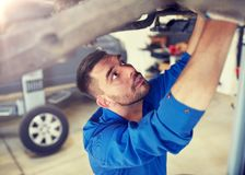 Mechanic man or smith repairing car at workshop royalty free stock photos