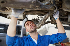 Mechanic man or smith repairing car at workshop. Car service, repair, maintenance and people concept - auto mechanic man or smith working at workshop stock image