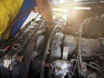 Mechanic man in uniform repairing car in garage. Auto repair service. Stock Photo