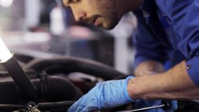 Mechanic man with wrench repairing car at workshop 58. Car service, repair, maintenance and people concept - mechanic man with wrench and lamp working at stock video