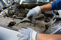 Mechanic man with wrench repairing car at workshop Stock Image