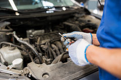 Mechanic man with wrench repairing car at workshop Royalty Free Stock Photos