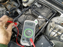 Mechanic measures charge voltage Stock Photography