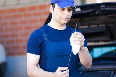 Mechanic measuring the oil level of an engine royalty free stock photo