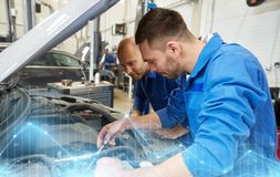 Mechanic men with wrench repairing car at workshop. Auto service, repair, maintenance and people concept - mechanic men with wrench repairing car at workshop Royalty Free Stock Images