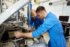 Mechanic men with wrench repairing car at workshop. Auto service, repair, maintenance and people concept - mechanic men with wrench repairing car at workshop Stock Photos