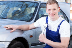 Mechanic with a monkey wrench. A smiling mechanic by a car holding a monkey wrench stock image