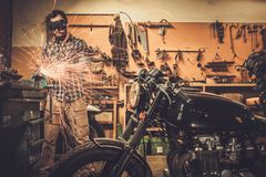 Mechanic at motorcycle customs garage. Mechanic doing lathe works in motorcycle customs garage royalty free stock image