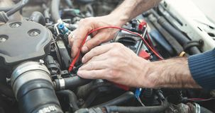 Mechanic with a multimeter testing car engine. Car service royalty free stock photography