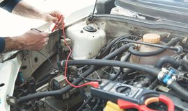 Mechanic with a multimeter testing car engine. Car service stock photography