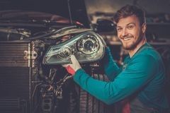 Mechanic with new car headlight in a workshop Royalty Free Stock Photos