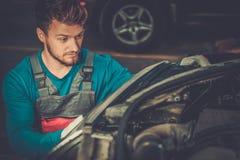 Mechanic with new car headlight Stock Photography