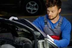 Mechanic with new car headlight Royalty Free Stock Image