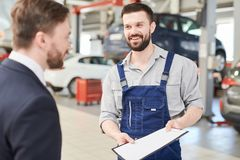 Mechanic Offering Contract to Client. Waist up portrait of smiling bearded mechanic talking to businessman standing in clean modern car service and repair center stock photography