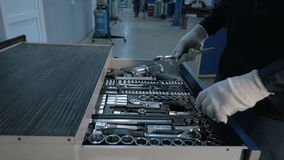 Mechanic open Blue Metal Box with Different Tools for Car Repair at Modern Service station