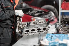 The mechanic opened the locking valve mechanism. Disassemble engine block vehicle. Motor capital repair. Sixteen valves. The mechanic installs a new valve Royalty Free Stock Photos