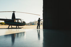 Mechanic opening the door of a airplane hangar. With a helicopter Stock Photos