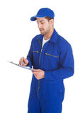 Mechanic In Overall Writing On Clipboard Royalty Free Stock Photo