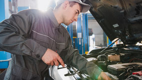 Mechanic in overalls checks level of engine oil in the car - automobile service repairing Royalty Free Stock Image