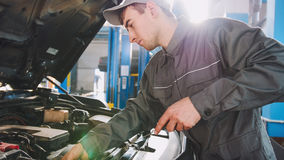 Mechanic in overalls checks level of engine oil in the car - automobile service repairing. Close up stock images