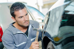 Mechanic panel beating car. Mechanic panel beating a car stock image