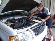Mechanic Performing a Routine Service Inspection Royalty Free Stock Photo