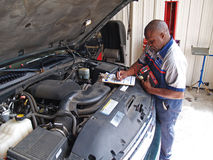 Mechanic Performing a Routine Service Inspection royalty free stock images