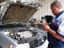 Mechanic Performing a Routine Service Inspection royalty free stock photos