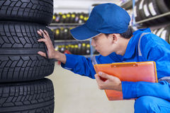 Mechanic person examining tires Royalty Free Stock Image