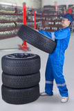 Mechanic piling up tires in the workshop. Male mechanic working in the workshop with blue uniform and piling up tires Royalty Free Stock Images