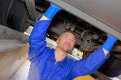 Mechanic in pit checking underneath vehicle. Mechanic in pit checking underneath of vehicle stock photo