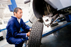 Mechanic placing a wheel Royalty Free Stock Photography