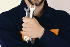 Mechanic or plumber with metallic spanner equipment in hand. Spanner instruments for fixing or tightening details. Maintenance and repairing concept. Man holds Royalty Free Stock Images