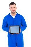 Mechanic pointing on digital tablet. Portrait of happy mechanic pointing on digital tablet on white background Stock Photo