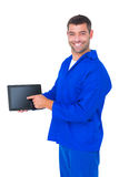 Mechanic pointing on digital tablet on white background. Portrait of happy mechanic pointing on digital tablet on white background Stock Images