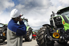 Mechanic pointing at large farming tractors. Mechanic, worker, pointing at large farming tractors, latest models Stock Photography