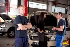 Mechanic Portrait. Mechanic looking at camera with customer and second mechanic in background Royalty Free Stock Photo
