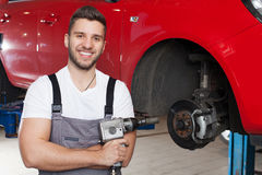 Mechanic posing with an impact wrench Royalty Free Stock Images